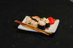 Les sushi de Nigiri ont placé du plat blanc sur le fond noir Nourriture japonaise Dîner savoureux asiatique Photo libre de droits