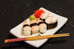 Les sushi de Nigiri ont placé du plat blanc sur le fond noir Nourriture japonaise Dîner savoureux asiatique Photo stock