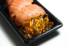 Les sushi saumonés ont servi avec le plan rapproché de pilules d'huile de poisson d'isolement Photos libres de droits