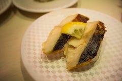 Les sushi 100 Yens du plat blanc dans le restaurant japonais à Tokyo Images stock