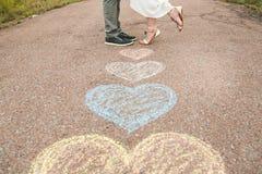 Les symboles de coeur ont formé avec des crayons sur la terre et deux personnes dans le lo Photo stock