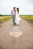 Les symboles de coeur ont formé avec des crayons sur la terre et deux personnes dans le lo Photographie stock libre de droits