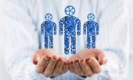 Les symboles verts des membres de la famille en tant qu'un mécanisme ont présenté dans des paumes de l'homme Photo libre de droits