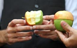 Les têtes tiennent une pomme verte et rouge Photo libre de droits