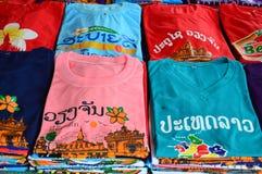 Les T-shirts colorés avec les attractions touristiques laotiennes examinent l'impression vendue à la boutique de souvenirs à Vien Images stock