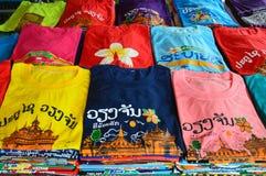 Les T-shirts colorés avec les attractions touristiques laotiennes examinent l'impression vendue à la boutique de souvenirs à Vien Photographie stock libre de droits