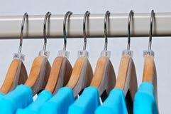Les T-shirts des femmes de turquoise de diverses tailles accrochant sur l'ha en bois Photographie stock libre de droits