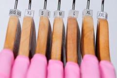 Les T-shirts des femmes roses de diverses tailles accrochant sur les cintres en bois Photos libres de droits