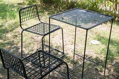 Les tables et les chaises extérieures ont installé sur la pelouse verte Image libre de droits