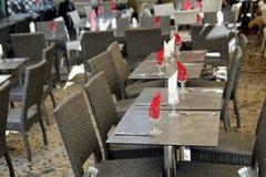 Les tables vides ont placé avec les serviettes rouges et blanches à un restau extérieur Photo stock