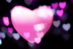 Les taches floues roses de coeur dans l'à l'extérieur-de-orientation s'allume Photos stock