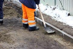Les tailleurs de pierres travaillants réparent le trottoir, installent des restrictions avant l'asphaltage pour la route Photographie stock libre de droits
