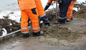Les tailleurs de pierres travaillants réparent le trottoir, installent des restrictions avant l'asphaltage pour la route Images stock