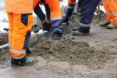 Les tailleurs de pierres travaillants réparent le trottoir, installent des restrictions avant l'asphaltage pour la route Images libres de droits