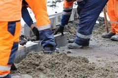 Les tailleurs de pierres travaillants réparent le trottoir, installent des restrictions avant l'asphaltage pour la route Photos libres de droits