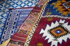 Les tapis de berber tissés par main colorée ont écarté sur le plancher de bazar au Maroc images stock