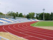 Les tapis roulants rouges, le fonctionnement de voie, herbe verte et vident des supports au stade, sur le ciel bleu Sport et form Photos stock