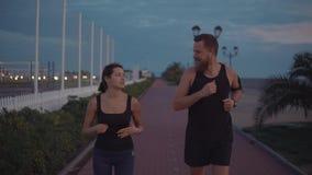 Les taqueurs d'homme et de femme flirtent pendant la soirée fonctionnant dehors, les visages heureux clips vidéos