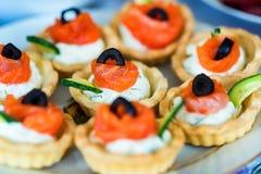 Les tartelettes avec du fromage, des saumons et des olives se ferment Images stock
