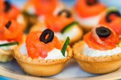 Les tartelettes avec du fromage, des saumons et des olives se ferment Photo libre de droits