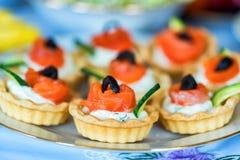 Les tartelettes avec du fromage, des saumons et des olives se ferment Image stock