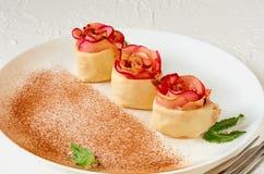 Les tartes roses de mini pomme du plat blanc ont décoré les feuilles en bon état et la poudre de cannelle Tarte végétarienne d'au photo stock