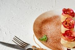 Les tartes roses de mini pomme du plat blanc ont décoré les feuilles en bon état et la poudre de cannelle Tartes végétariennes d' photographie stock libre de droits