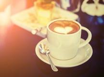 Les tasses blanches de café de cappuccino avec du lait en forme de coeur écument Images libres de droits