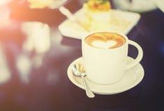 Les tasses blanches de café de cappuccino avec du lait en forme de coeur écument Sel Photographie stock