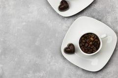Les tasses blanches pour l'expresso ont rempli de grains de café et de chocolat i Image libre de droits
