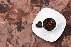 Les tasses blanches pour l'expresso ont rempli de grains de café et de chocolat i Images stock