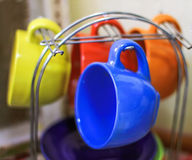 les tasses colorées lumineuses sur un appui metal des plats à la maison photo libre de droits
