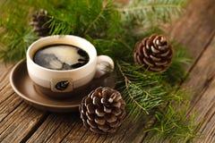 Les tasses de café à côté des cônes et un pin s'embranchent photos stock