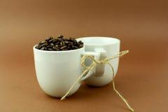 Les tasses de café avec un arc et les grains de café brunissent le fond Images libres de droits
