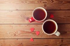 Les tasses de thé romantiques avec le coeur forment sur la table en bois Vue de ci-avant Image libre de droits