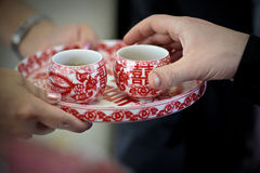 Les tasses de thé rouges traditionnelles chinoises de cérémonie de thé de mariage sur la portion de jeune mariée de plateau engen Photo stock