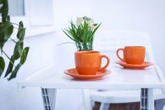 Les tasses oranges avec du café ou le thé chaud ont servi sur une table blanche Image libre de droits