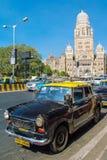 Les taxis conduisent sur une rue dans Mumbai, Inde Photographie stock libre de droits
