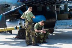 Les techniciens inspectent l'hélicoptère de combat avec les capacités de transport le mil Mi-24 de derrière Image stock