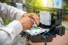 Les techniciens installent le coffret sur le câble optique de fibre Image stock