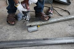 Les techniciens utilisent des foreuses de tuyau en m?tal photo stock