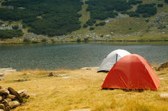 Les tentes campantes s'approchent d'un lac de montagne Photographie stock