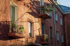 Les terrasses et les fenêtres de la vieille maison rouge photo stock