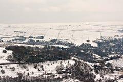 Les terres cultivables lointaines sur la neige couverte amarrent photographie stock