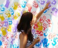 Les timbres de fille tracent des mains sur le mur avec des copies Image libre de droits