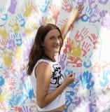 Les timbres de fille tracent des mains sur le mur avec des copies Photo stock