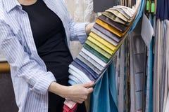 Les tissus stockent, femelle regardant et touchant des échantillons, le concepteur féminin choisit des tissus pour la décoration  images libres de droits