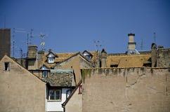 Les toits avec des greniers, des bardeaux rouges et des antennes sur le fond de ciel bleu image libre de droits