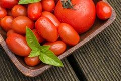Les tomates avec de l'eau se laisse tomber dans une cuvette en bois Images libres de droits