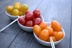 Les tomates-cerises dans un casse-croûte roulent sur le fond en bois Photo libre de droits